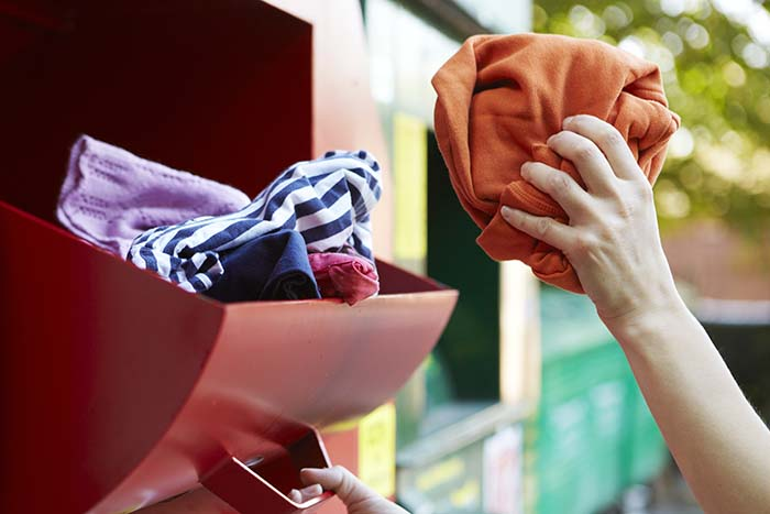 Woman Recycling Clothes At Clothing Bank