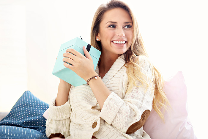 Picture showing happy woman opening present at home
