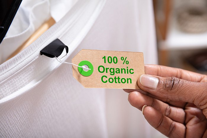 Close-up Of A Woman's Hand Holding Label Showing 100 Percent Organic Cotton